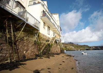 Steps leading down to the sandy water's edge from the balcony at Barnacles, Fowey