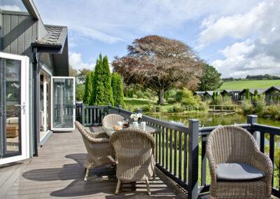 The wraparound deck with lake views at Combe Lodge, Kentisbury Grange, Kentisbury