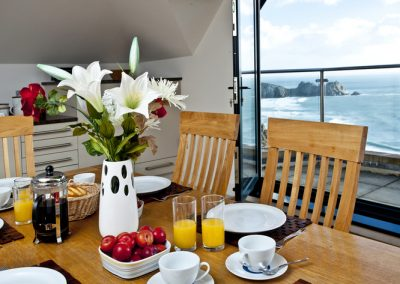 The dining area opens onto a balcony with stunning views @ The Penthouse, Porthcurno, Penzance