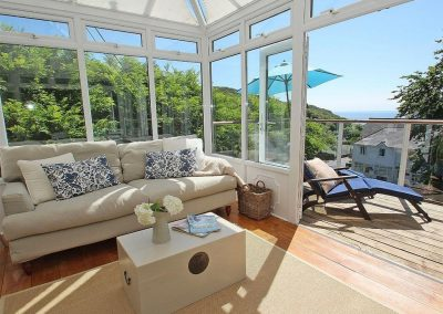 The sun-filled conservatory at Porthcurno Bay View, Porthcurno