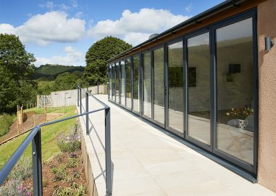 A staggering 16 metres of bi-fold doors opening out to a tiled balcony overlooking the beautiful garden & river at Teign Vale, Drewsteignton