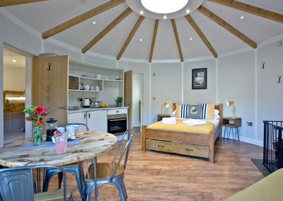 The open-plan dining, kitchen & sleeping area at The Boat House Roundhouse, East Thorne, Kilkhampton