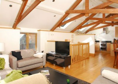 The living area @ Wells Park Barn features a vaulted ceiling with beautiful exposed beams