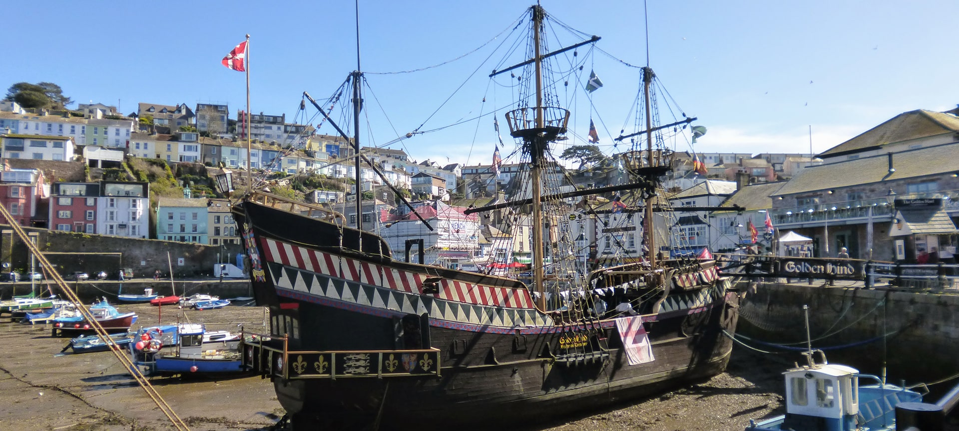 Located at the old fishing port of Brixham is The Golden Hind, a full sized and permanently moored replica of one of the most iconic exploration ships and a landmark tourist attraction in the town since 1964. Through the replica's five decks it tells the story of the life and times of the captain and crew along with conditions at sea during the 1600s through various exhibitions, re-enactments and interactive sessions. The idea is to allow visitors to really experience the sights, sounds and smells of life aboard a Tudor ship.